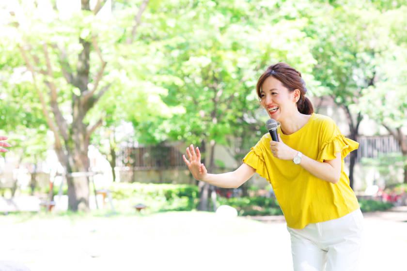 写真:片手をあげている笑顔のイベントMC