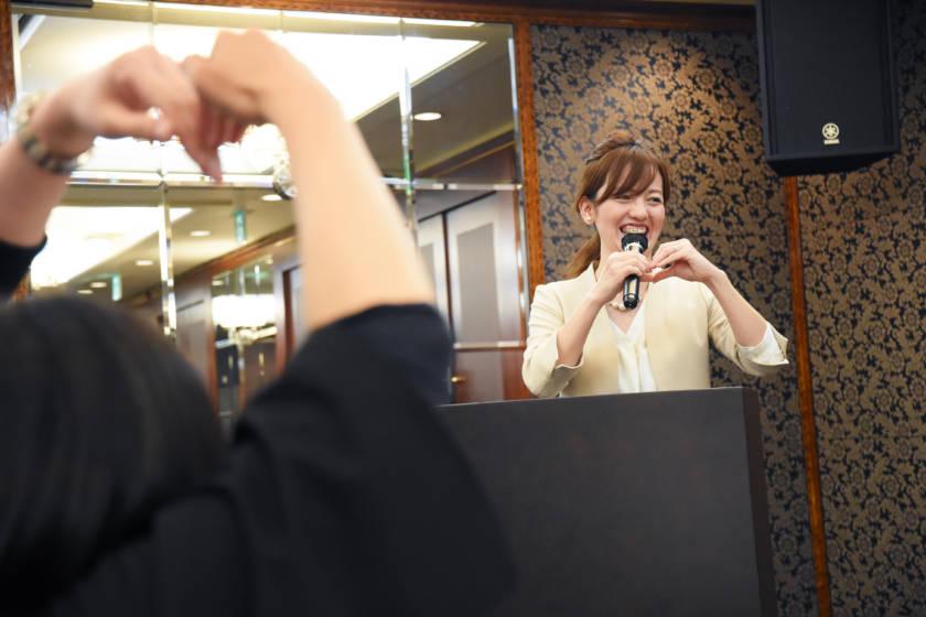 写真:手でハートマークを作った笑顔のMC